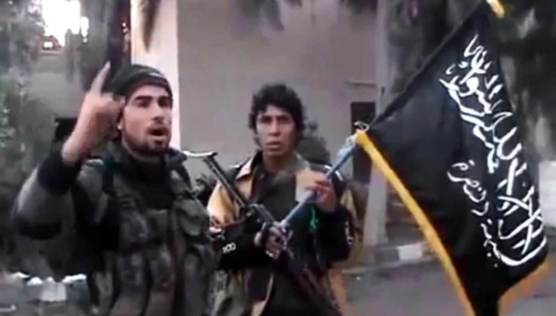 In this image taken from video obtained from the Ugarit News, which has been authenticated based on its contents and other AP reporting, a Free Syrian Army fighter speaks in front of a government intelligence complex in Deir el-Zour, Syria, on Tuesday, Jan. 29, 2012. (AP Photo/Ugarit News via AP video)