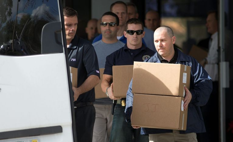 Federal law enforcement officials carry boxes Jan. 30, 2013, out of the offices of Dr. Salomon Melgen in West Pa