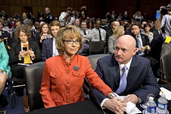 ** FILE ** Former Rep. Gabrielle Giffords, who was seriously injured in a mass shooting that killed six people in Tucson, Ariz., in 2011, sits with her husband, Mark Kelly, a retired astronaut, on Capitol Hill in Washington on Wednesday, Jan. 30, 2013, before speaking before the Senate Judiciary Committee hearing on what lawmakers should do to curb gun violence in the wake of the December
