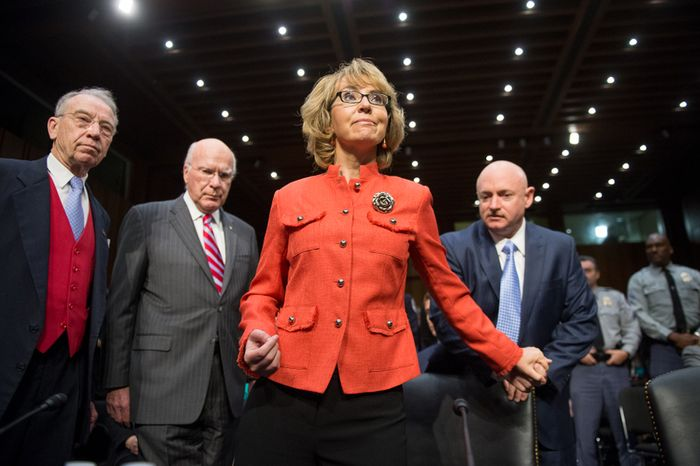 From left, Sen. Chuck Grassley, Iowa Republican, and Sen. Patrick J. Leahy, Vermont Democrat, accompany Ms. Giffords as she and Mr. Kelly arrive to testify at the committee hearing. (Andrew Harnik/The Washington Times)