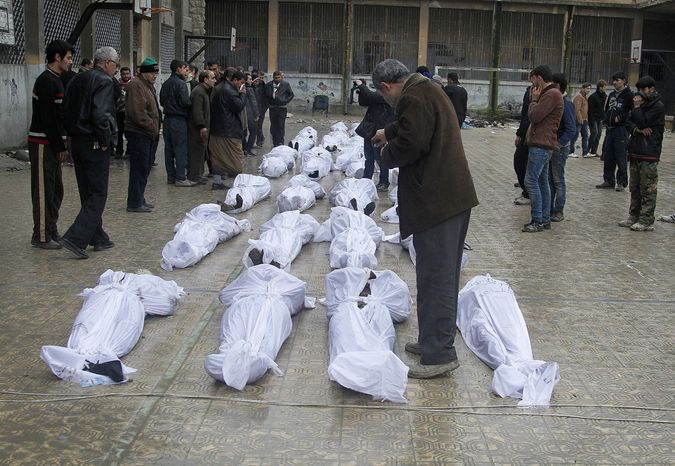 Syrian citizens search Jan. 30, 2013, in the neighborhood of Bustan al-Qasr in Aleppo for their relatives amongst dead bodies f