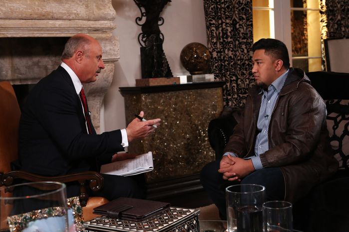 """Talk show host Dr. Phil McGraw (left) interviews Ronaiah Tuiasosopo on Jan. 24, 2013, during taping for the """"Dr. Phil Show"""" in Los Angeles. The two-part program, scheduled to air Jan. 31 and Feb. 1, is the first on-air interview of Tuiasosopo, the man who allegedly concocted the girlfriend hoax that ensnared Notre Dame football star Manti Te'o. (Associated Press/CBS Television Distribution/Peteski Productions)"""