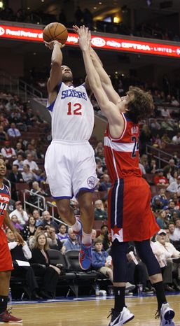 Washington Wizards' Jan Vesely (24) defends as Philadelphia 76ers' Evan Turner shoots during the first half of the 76ers' 92-84 win on Jan. 30, 2013, in Philadelphia. (Associated Press)
