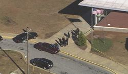 """In this image made from video and released by WSB-TV, authorities investigate the scene of a school shooting on Jan 31, 2013 in Atlanta. Authorities say a 14-year-old has been wounded in a shooting at an Atlanta middle school and a suspect has been taken into custody. Atlanta police spokesman Carlos Campos says the wounded student has been taken """"alert, conscious and breathing"""" to Grady Hospital. (Associated Press/WSB-TV)"""