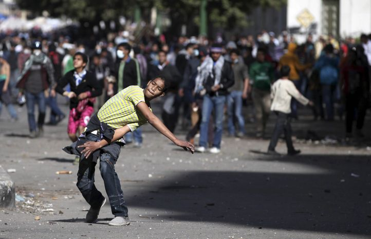 An Egyptian protester throws stones at riot police, not seen, during clashes near Tahrir Square in Cairo, Egypt, Wednesday, Jan. 30, 2013. (AP Photo/Khalil Hamra)