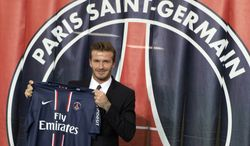 British soccer player David Backham, poses with his new jersey in front of the PSG logo during a press conference, at the Parc des Princes stadium in Paris, Thursday, Jan. 31, 2013. David Beckham will join Paris Saint-Germain on Thursday, opting for a move to France after mulling over lucrative offers from around the world since leaving the Los Angeles Galaxy.(AP Photo/Michel Euler)