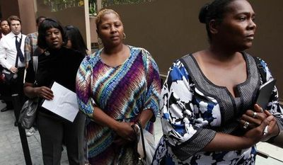 **FILE** Sheila Bird (right) waits in line for employment interviews at a Aug. 17, 2012, job fair at City Target in Los Angeles. (Associated Press)