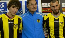 Beitar Jerusalem F.C. soccer coach Eli Cohen, center, poses for the media with new Beitar players Gabriel Kadiev, left, and Zaur Sadayev, right, during a press conference in Jerusalem, Wednesday, Jan. 30, 2013. The arrival of Zaur Sadayev and Gabriel Kadiev to Beitar Jerusalem's squad comes amid rising tensions. The team's fans chanted anti-Muslim slogans at a recent game and unfurled a sign protesting the Chechens' arrival. (AP Photo/Bernat Armangue)