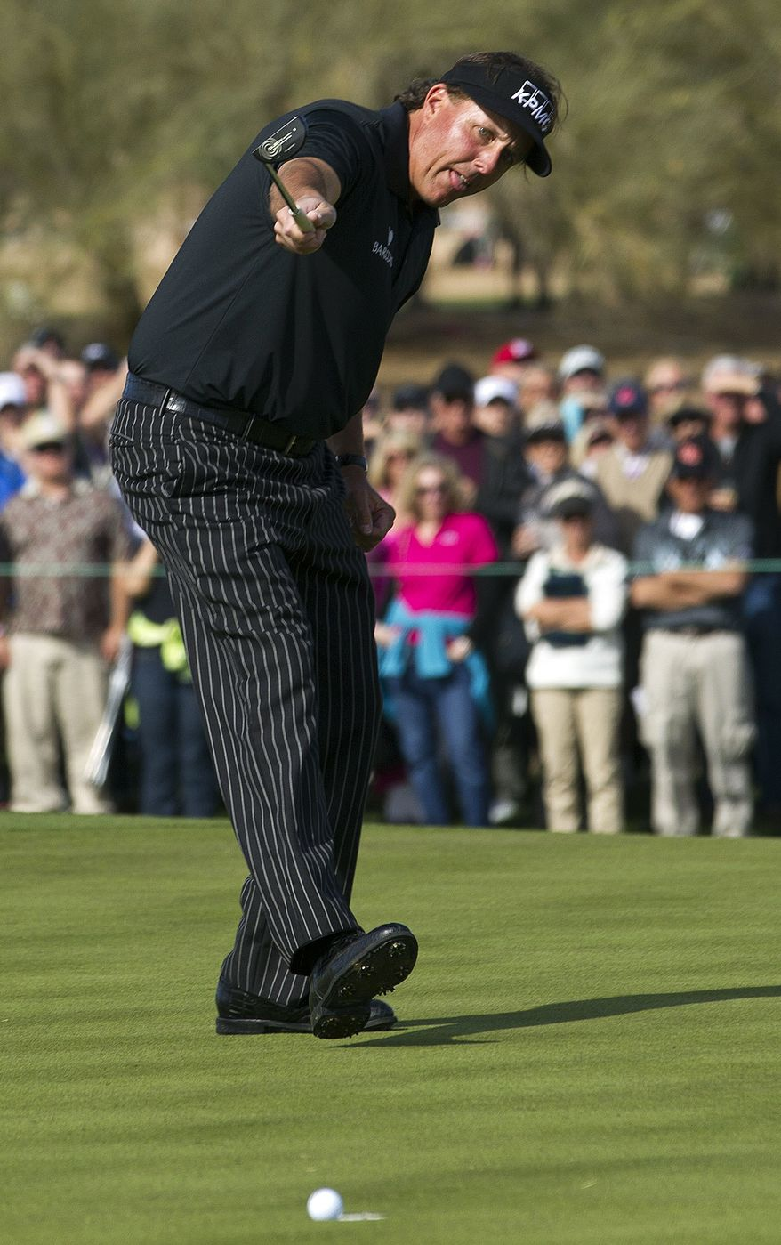 Phil Mickelson watches his birdie putt roll towards the cup on the ninth green during first round of the Phoenix Open golf tournament, Thursday, Jan. 31, 2013, in Scottsdale, Ariz. Mickelson's putt lipped-out, and he had to settle for par on the hole. (AP Photo/The Arizona Republic, Rob Schumacher)