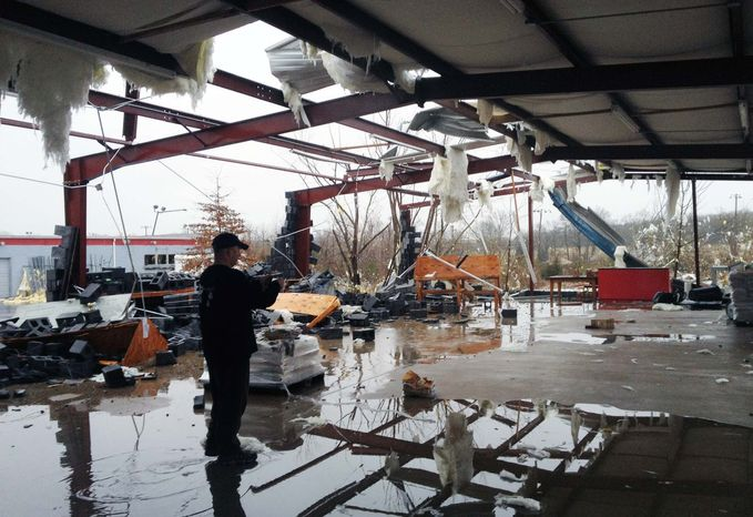 Tennessean employee Joel Procter takes photographs of the what is left of the building where he was working on Wednesday, Jan 30. 2013, in Mt. Juliet, Tenn. A tornado tore through businesses and stores in Mount Juliet early Wednesday. (AP Photo/The Tennessean, Shelley Mays)