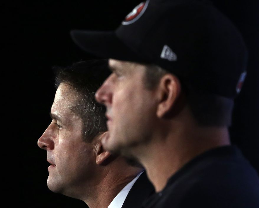 **FILE** Baltimore Ravens head coach John Harbaugh (left) and his younger brother, San Francisco 49ers head coach Jim Harbaugh, participate in a Feb. 1, 2013, news conference in New Orleans for Super Bowl XLVII. (Associated Press)