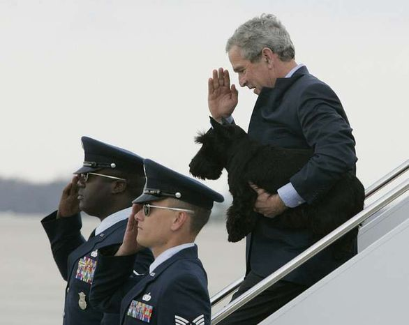 President Bush, carrying his dog Barney, salutes airmen as he disembarks Air Force One at Andrews Air Force Base, Md., after returning from Cincinnati, Ohio, Monday, April 3, 2006. (Associated Press) ** FILE **