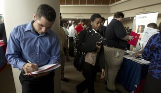 **FILE** Fernando Rames answers questions on a job application at the job fair in Sunrise, Fla., Jan. 22, 2013. (Associated Press)