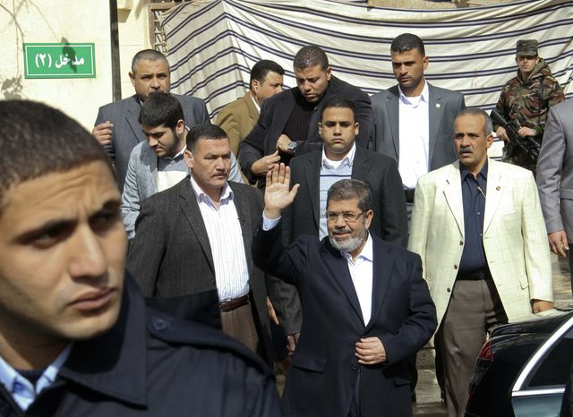 Egyptian President Mohammed Morsi, center, waves after attending Friday prayers in Cairo, Egypt, Feb. 1, 2013. Thousands of Egyptians marched across the country, chanting against the rule of Morsi. (AP Photo/Jihan Nasr, Shorouk Newspaper)