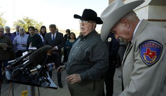 David Byrnes, sheriff of Kaufman County, right, bows his head as Mike McLelland, district attorney of Kaufman County, answers questions at a news conference at the Kaufman Law Enforcement Center on Thursday, Jan. 31, 2013, in Kaufman, Texas. (AP Photo/The Dallas Morning News, David Woo)