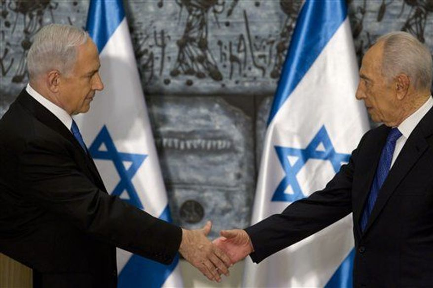 Israeli Prime Minister Benjamin Netanyahu, left, shakes hands with Israeli President Simon Peres during a brief ceremony in the president' Jerusalem residence Saturday Feb. 2, 2013. (Associated Press)