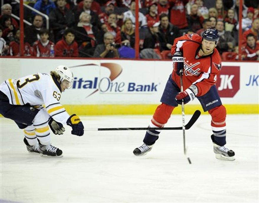 Washington Capitals defenseman John Erskine (4) works the puck against Buffalo Sabres left wing Tyler Ennis (63) during the second period of an NHL hockey game, Sunday, Jan. 27, 2013, in Washington. (AP Photo/Nick Wass)