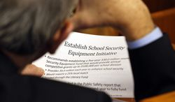 Del. Charles Poindexter (R-Patrick) looks over details of a house subcommittee recommendations on funding school security measures included in the House budget bill during a Sunday legislative session in Richmond, Feb. 3, 2013. (AP Photo/The Richmond Times-Dispatch, Joe Mahoney)