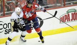 Washington Capitals left wing Alex Ovechkin (8), of Russia, battles for the puck along the boards against Pittsburgh Penguins center Sidney Crosby (87) during the third period of an NHL hockey game on Sunday, Feb. 3, 2013, in Washington. The Penguins won 6-3. (AP Photo/Nick Wass)