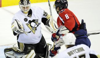 Pittsburgh Penguins goalie Tomas Vokoun (92) looks at the puck as Washington Capitals left wing Alex Ovechkin (8) looks on during the third period of an NHL hockey game on Sunday, Feb. 3, 2013, in Washington. The Penguins won 6-3. (AP Photo/Nick Wass)