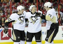 Pittsburgh Penguins left wing Chris Kunitz, center, celebrates his goal with teammate Sidney Crosby (87) and Evgeni Malkin (71), of Russia, during the second period of an NHL hockey game on Sunday, Feb. 3, 2013, in Washington. (AP Photo/Nick Wass)