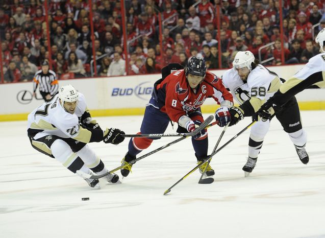 Washington Capitals left wing Alex Ovechkin (8) chases after the puck against Pittsburgh Penguins players Craig Adams (27) and Kris Letang (58) during the first period of an NHL hockey game on Sunday, Feb. 3, 2013, in Washington. (AP Photo/Nick Wass)
