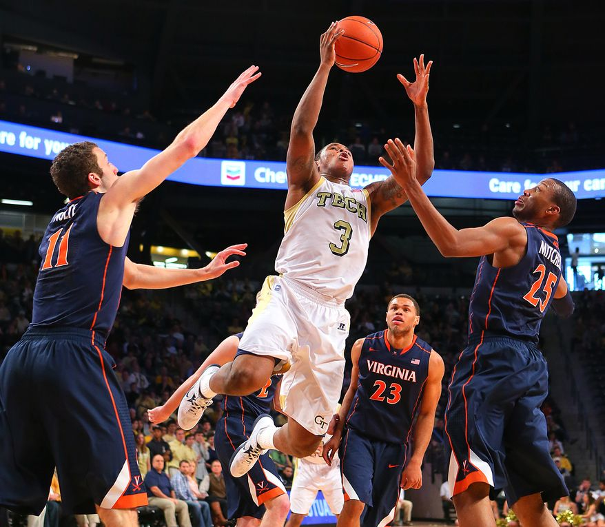 Georgia Tech guard Marcus Georges-Hunt leaps for a rebound over Virginia defenders Evan Nolte, left, Justin Anderson (23) and Akil Mitchell during the second half of their NCAA college basketball game on Sunday Feb. 3, 2013, in Atlanta. Georgia Tech battled back for a come from behind 66-60 victory to end Virginia's winning streak. (AP Photo/Atlanta Journal-Constitution, Curtis Compton)