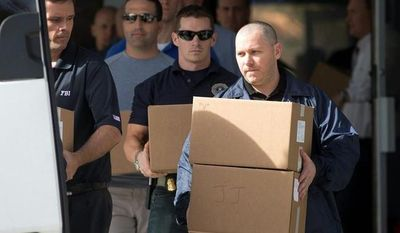Federal law enforcement officials carry boxes Jan. 30, 2013, out of the offices of Dr. Salomon Melgen in West Palm Beach, Fla. (Associated Press)
