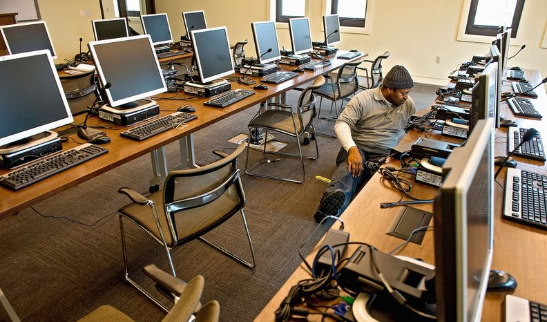 Getting ready for the new USO center's debut, technician Matthew Hammond with AVC wires computers in a classroom. (Andrew Harnik/The Washington Times)