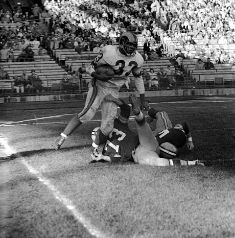 **FILE** Los Angeles Rams' fullback Ollie Matson (33) goes into the end zone for a touchdown in the fourth quarter of the game against the Green Bay Packers in Milwaukee, Wisc., Oct. 19, 1959. On the ground are tackle Ken Beck (73) and back Dan Currie. Rams won 45-6. (AP Photo)