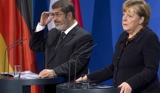 German Chancellor Angela Merkel (right) and Egyptian President Mohammed Morsi address the media during a joint press conference after a meeting at the Chancellery in Berlin on Wednesday, Jan. 30, 2013. (AP Photo/Michael Sohn)