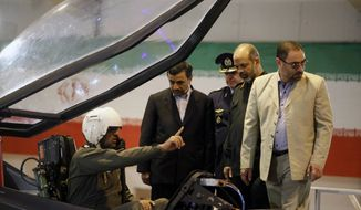 Iranian President Mahmoud Ahmadinejad, center, listens to an unidentified pilot during a ceremony to unveil Iran's newest fighter jet, Qaher-313, or Dominant-313,which officials claim can evade radar, in Tehran, Iran, Saturday, Feb. 2, 2013. (AP Photo/Mehr News Agency, Younes Khani)