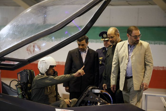 Iranian President Mahmoud Ahmadinejad, center, listens to an unidentified pilot during a ceremony to unveil Iran's newest fighter jet, Qaher-313, or Dominant-313,which officials claim can evade radar, in Tehran, Iran, Saturday, Feb. 2, 2013. (AP Photo/Mehr New