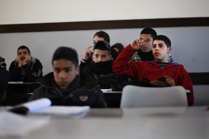 Palestinian students attend class in a school in the West Bank city of Ramallah on Sunday, Feb. 3, 2013. (AP Photo/Majdi Mohammed)