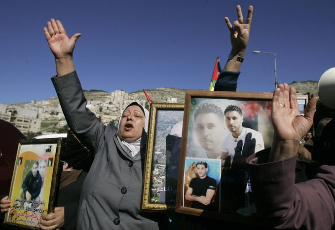 Palestinian women hold pictures of prisoners jailed in Israel during a rally calling for their release, in the West Bank city of Nablus, Monday, Feb. 4, 2013. Israeli forces arrested 20 members of the Palestinian militant group Hamas, including three lawmakers, in a raid early Monday in the West Bank, Hamas officials said. (AP Photo/Nasser Ishtayeh)