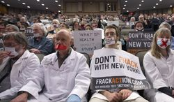 **FILE** Opponents of hydraulic fracturing, or fracking, demonstrate Jan. 30, 2013, in Albany, N.Y., as they sit in the audience as Dr. Nirav Shah, commissioner of the New York State Department of Health, testifies before a joint budget hearing on health and Medicaid. (Associated Press)