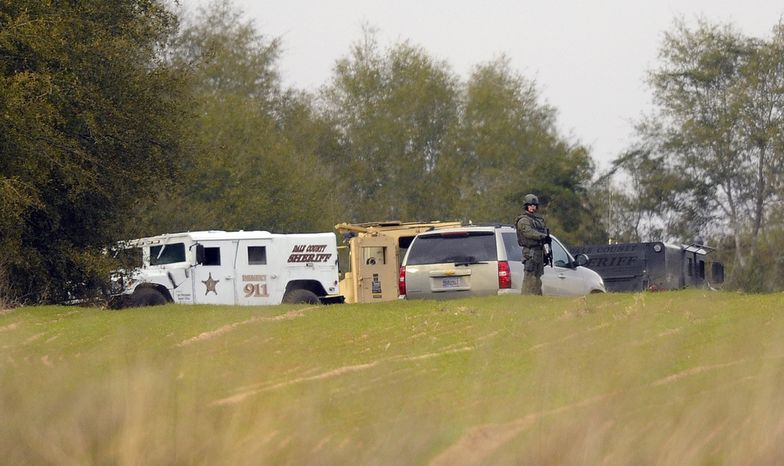 Armed law enforcement personnel station themselves on Feb. 4, 2013, near the property of Jimmy Lee Sykes in Midland City, Ala. Officials say they stormed a bunker in Alabama to rescue a 5-year-old child being held hostage there after Sykes, his abductor, was seen with a gun. (Associated Press/AL.com, Joe Songer)