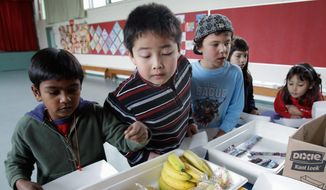 ** FILE ** Second-grader Jonathan Cheng (center) looks at fruits and vegetables during a school lunch at Fairmeadow Elementary School in Palo Alto, Calif., on Dec. 2, 2010. (Associated Press)