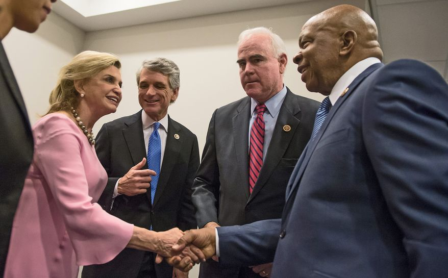 Reps. Carolyn B. Maloney (from left), New York Democrat; E. Scott Rigell, Virginia Republican; Patrick Meehan, Pennsylvania Republican; and Elijah E. Cummings, Maryland Democrat, prepare Tuesday to announce legislation to make firearms trafficking a federal crime and stiffen laws against straw buyers. (Andrew Harnik/The Washington Times)