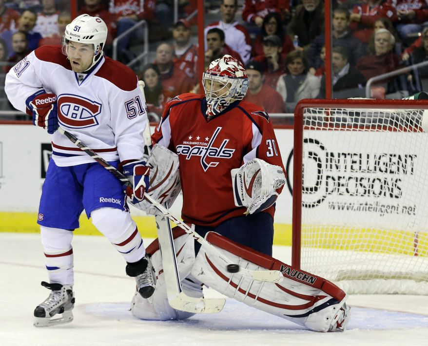 Montreal Canadiens center David Desharnais (51) lets the puck go by for a goal by teammate defenseman Josh Gorges as Washington Capitals goalie Michal Neuvirth (30) from the Czech Republic, cannot make the stop in the second period of an NHL hockey game on Thursday, Jan. 24, 2013, in Washington. (AP Photo/Alex Brandon)
