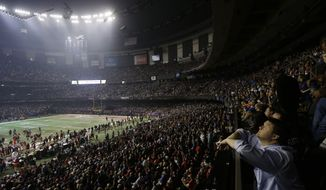 **FILE** Fans and members of the Baltimore Ravens and the San Francisco 49ers wait for power to return in the Superdome during an outage in the second half of Super Bowl XLVII on Feb. 3, 2013, in New Orleans. (Associated Press)