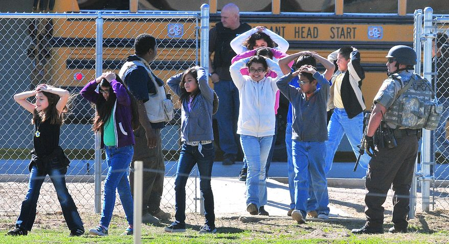 Students from Salida Del Sol Elementary School are evacuated to the school cafeteria by police officers after three schools went into lockdown on Tuesday, Feb. 5, 2013, in Yuma, Ariz. The unconfirmed report of a person with a gun initially prompted the lockdown, but no gun was found. (AP Photo/The Yuma Sun, Craig Fry)