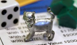 """A cat, resting on a Boardwalk deed, will soon the one of the tokens in Monopoly. The cat got 31 percent of the vote on Facebook to determine the winner of an online """"election."""" The iron, part of the game since 1935, was voted off the board. (Associated Press)"""
