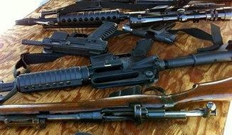 **FILE** Guns are offered during a buyback program on Jan. 26, 2013, in San Mateo, Calif. Authorities are offering up to $100 cash for a handgun, shotgun or rifle, or up to $200 for an assault rifle at the event at the San Mateo Event Center. (Associated Press)