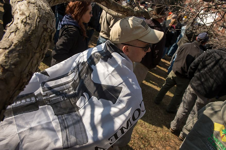 "A man who did not want to give his name wears a flag with an assault riffle on it and the words, ""Come and Take It"" at a pro-gun rights rally at Lawyers Park in front of the Maryland State House, Annapolis, Md., Wednesday, February 6, 2013. Maryland Mayor Martin O'Malley is set to testify  at a Judicial Proceedings Committee hearing that are discussing a number of proposed gun bills. (Andrew Harnik/The Washington Times)"