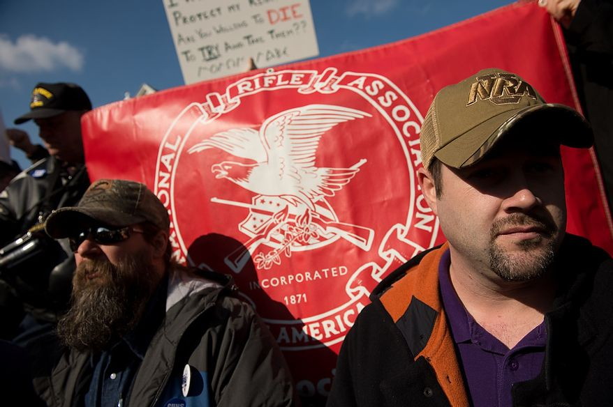Tom Thompson of Glen Burnie, Md., left, and Jeff Richards of Easton, Md., right, stands in front of a National Rifle Association banner at a pro-gun rights rally against a proposal by Maryland Governor Martin O'Malley that would ban assault weapons and require residents to obtain a license before purchasing handguns at Lawyers Park in front of the Maryland State House, Annapolis, Md., Wednesday, February 6, 2013. (Andrew Harnik/The Washington Times)