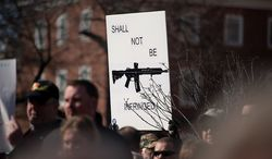 **FILE** A sign depicting an assault rifle is held up at a pro-gun rights rally against a proposal by Maryland Gov. Martin O'Malley that would ban assault weapons and require residents to obtain a license before purchasing handguns at Lawyers Park in front of the Maryland State House in Annapolis on Feb. 6, 2013. (Andrew Harnik/The Washington Times)