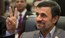** FILE ** Iranian President Mahmoud Ahmadinejad flashes the victory sign as he attends the 12th summit of the Organization of Islamic Cooperation in Cairo on Wednesday, Feb. 6, 2013. (AP Photo/Amr Nabil)