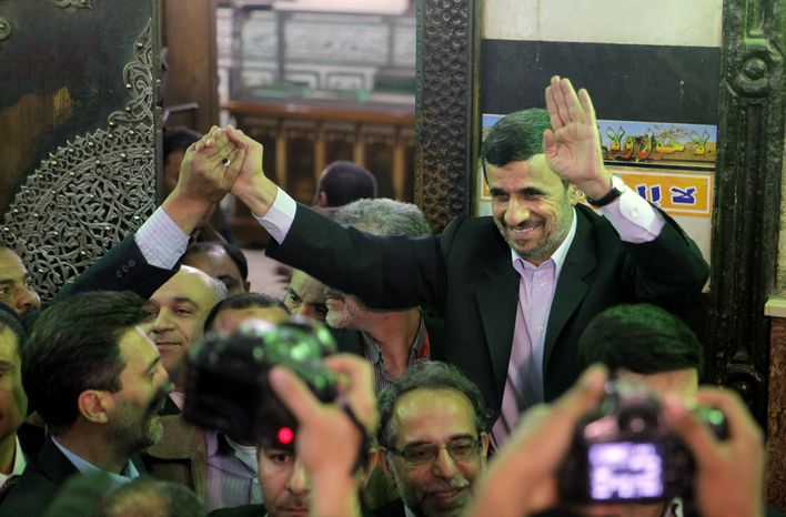 Iran's President Mahmoud Ahmadinejad, center, waves to Egyptians worshippers in front of the shrine of Imam Hussein, the grandson of Islam's Prophet M
