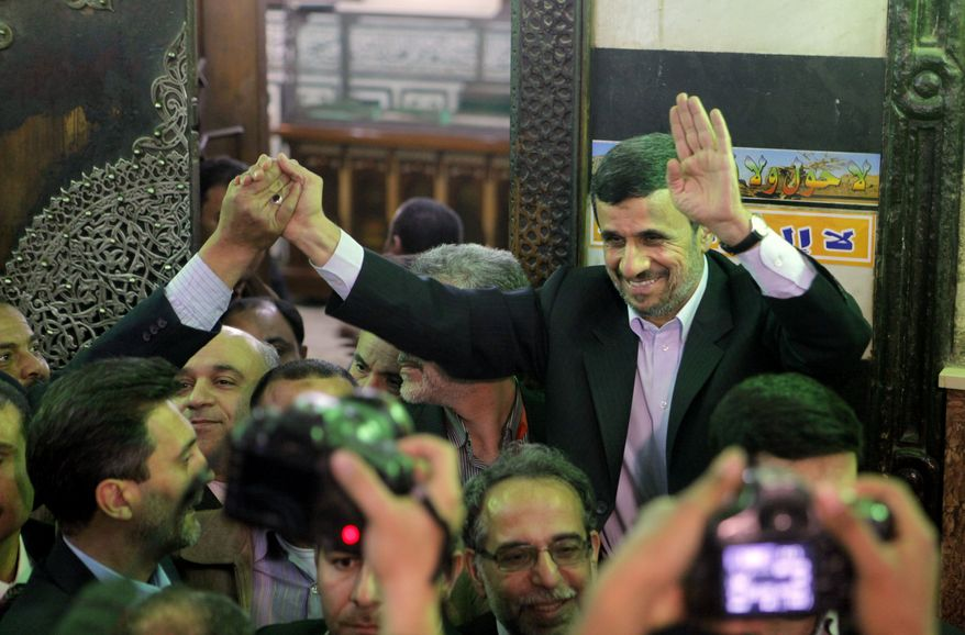 Iran's President Mahmoud Ahmadinejad, center, waves to Egyptians worshippers in front of the shrine of Imam Hussein, the grandson of Islam's Prophet Mohammad, in Cairo, Egypt, Tuesday, Feb. 5, 2013. (AP Photo/Amr Nabil)